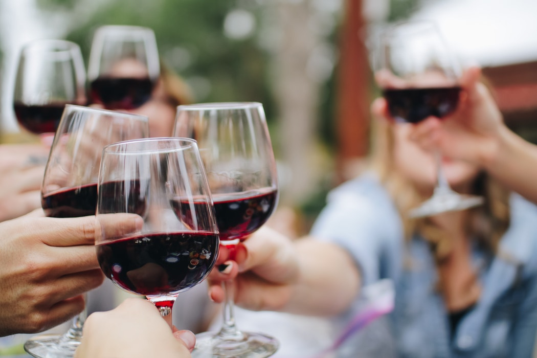 People drinking wine and cheersing